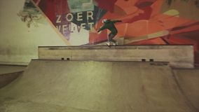 四轮溜冰者在跳板的尝试在竞争的跃迁与发怒feets,但是无法在skatepark 股票视频