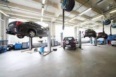 四辆汽车在推力和在小服务站的地板上。 库存图片