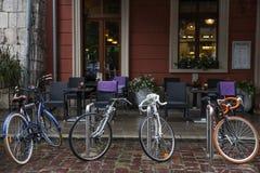 四辆自行车在咖啡馆的前面在雨中停放了 库存照片