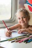 四年女孩画一张桌的铅笔图在一个第二等的火车支架的 免版税库存图片