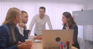 四collleagues会议画象在户内办公室 使用膝上型计算机和有讨论的商人  影视素材