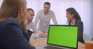 四collleagues会议画象在户内办公室 使用膝上型计算机的商人有绿色屏幕的和 影视素材
