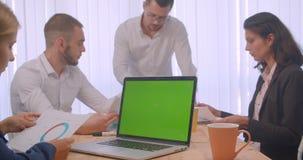 四collleagues会议画象在户内办公室 使用膝上型计算机的商人有绿色色度钥匙的 影视素材