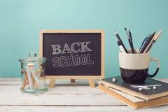 回到与书、铅笔在杯子和黑板的学校概念 免版税库存照片