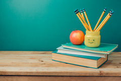 回到与书、铅笔在emoji瓶子和苹果的学校概念 库存照片