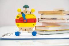 回到与书和闹钟的学校背景在黑板 12个o `时钟 时间安排概念 闹钟特写镜头 免版税库存照片