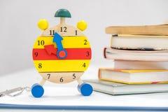 回到与书和闹钟的学校背景在黑板 12个o `时钟 时间安排概念 闹钟特写镜头 库存图片