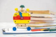 回到与书和闹钟的学校背景在黑板 12个o `时钟 时间安排概念 闹钟特写镜头 免版税库存图片
