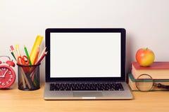 回到与便携式计算机和书的学校背景 现代工作场所 库存照片