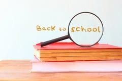 回到与堆的学校背景书和放大镜 免版税库存照片