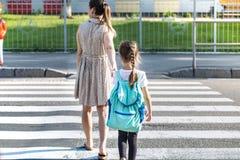 回到与女孩孩子的学校教育概念,小学生,去运载的背包分类 免版税库存图片