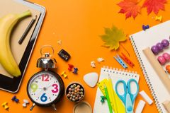 回到与时钟颜色白垩铅笔苹果笔记本的学校概念在黑板背景 库存照片