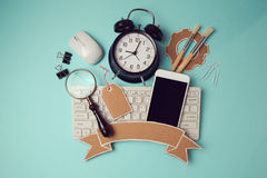 回到与智能手机、键盘和时钟的校徽设计 创造性的设计英雄倒栽跳水图象 库存照片
