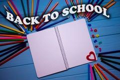 回到在明亮的五颜六色的铅笔的学校课文在与白色笔记本的蓝色木桌上 背景五颜六色的学校 免版税库存照片