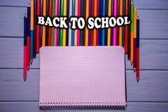 回到在明亮的五颜六色的铅笔的学校课文在与白色笔记本的蓝色木桌上 库存图片