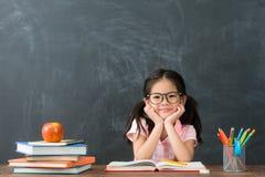 回到坐在类的学校的小孩女孩 免版税库存图片