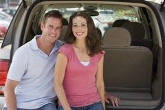 回到夫妇坐的微笑的有篷货车 免版税库存图片