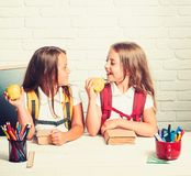 回到学校和家教 女孩吃苹果在午休时间 上课时间女孩 友谊小 免版税图库摄影