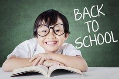回到学校和微笑的逗人喜爱的小女孩 免版税库存图片