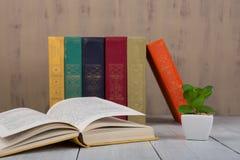 回到学校和教育概念-在白色木桌上的堆五颜六色的精装书书在棕色背景 库存图片