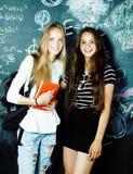 回到学校在暑假以后,两个青少年的女孩在有一起被绘的黑板的教室 免版税库存照片