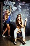 回到学校在暑假以后,两个青少年的女孩在有被绘的黑板的教室 库存图片