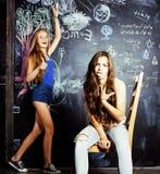 回到学校在暑假以后,两个青少年的女孩在有被绘的黑板的教室 图库摄影