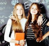 回到学校在暑假以后,两个青少年的真正的女孩在有一起被绘的黑板的教室,真正的生活方式 免版税库存照片