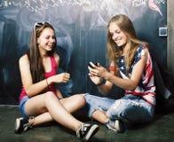 回到学校在暑假以后,分类的两个青少年的真正的女孩 免版税库存照片