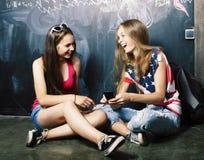 回到学校在暑假以后,分类的两个青少年的真正的女孩 免版税库存图片