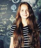 回到学校在暑假以后,逗人喜爱的青少年的真正的女孩在教室 图库摄影