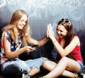 回到学校在暑假以后,两个青少年的真正的女孩在有一起被绘的黑板的教室,生活方式 免版税库存照片