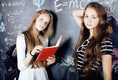 回到学校在暑假以后,两个青少年的真正的女孩在有一起被绘的黑板的教室 库存图片