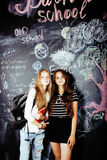 回到学校在暑假以后,两个青少年的真正的女孩在有一起被绘的黑板的教室 免版税库存照片