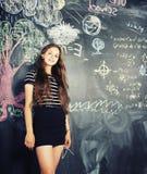 回到学校在暑假以后,逗人喜爱的青少年的女孩在教室 免版税图库摄影