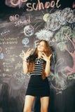 回到学校在暑假以后,逗人喜爱的青少年的真正的深色的女孩在黑板的,生活方式人概念教室 免版税库存图片