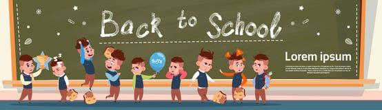 回到学校小组小站立在类板女小学生和男小学生教育横幅的学生女孩和男孩 免版税库存照片