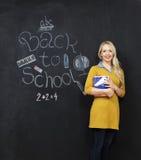 回到学校微笑由黑板的妇女老师 免版税库存图片