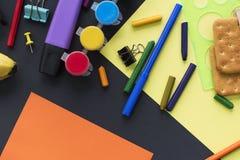回到学校手表粉笔线在黑背景的曲奇饼文具的概念 库存照片