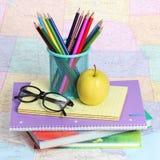 回到学校概念。一块苹果、色的铅笔和玻璃在堆书在地图 免版税库存图片