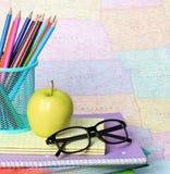 回到学校概念。一块苹果、色的铅笔和玻璃在堆书在地图 图库摄影