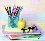 回到学校概念。一块苹果、色的铅笔和玻璃在堆书在地图 库存照片