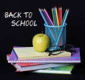 回到学校概念。一块苹果、色的铅笔和玻璃在堆书在黑背景 免版税图库摄影