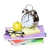 回到学校概念。一块苹果、闹钟和玻璃在白色隔绝的堆书 免版税图库摄影