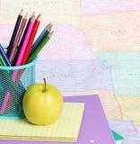 回到学校概念。一支苹果和色的铅笔在堆书在地图 库存照片