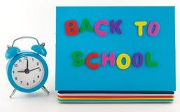 回到学校概念。闹钟、笔记本和铅笔 库存图片