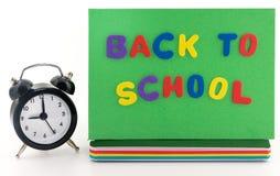 回到学校概念。闹钟、笔记本和铅笔 免版税库存照片