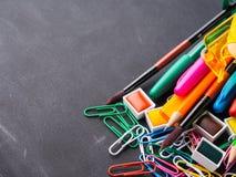 回到学校概念的五颜六色的文具在黑暗 免版税库存图片