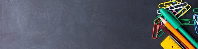 回到学校概念的五颜六色的文具在黑暗 图库摄影