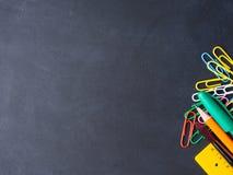 回到学校概念的五颜六色的文具在黑暗 免版税库存照片